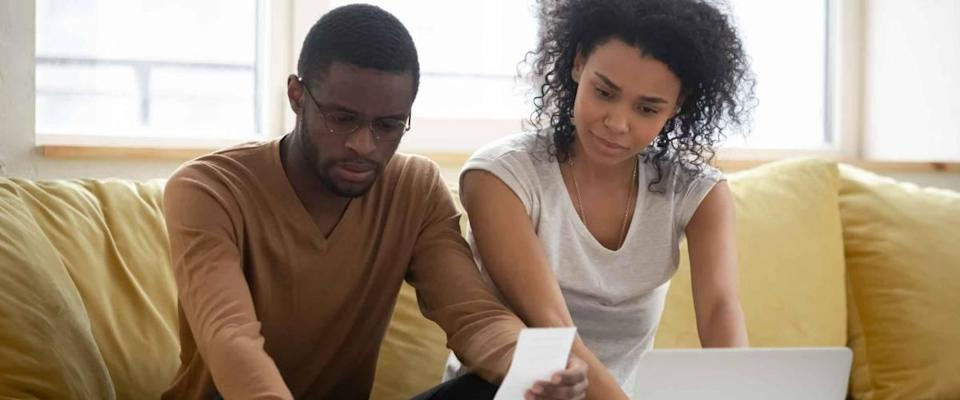 Serious african american couple using calculator and laptop for calaulating finance. Diverse upset man and woman taxing, accounting with check credit analytic for mortgage payment.