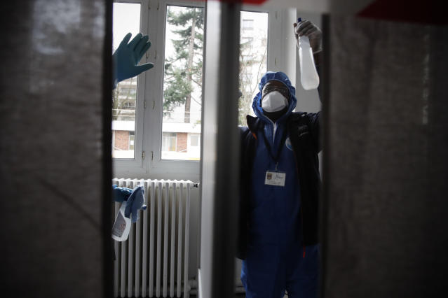 Workers wearing protective gears uses disinfectant to clean a voting booth as a precautionary measure against COVID-19 on the eve of the municipal elections in a Neuilly-sur-Seine polling station, outside Paris, Saturday, March 14, 2020. For most people, the new coronavirus causes only mild or moderate symptoms. For some it can cause more severe illness, especially in older adults and people with existing health problems. (AP Photo/Christophe Ena)