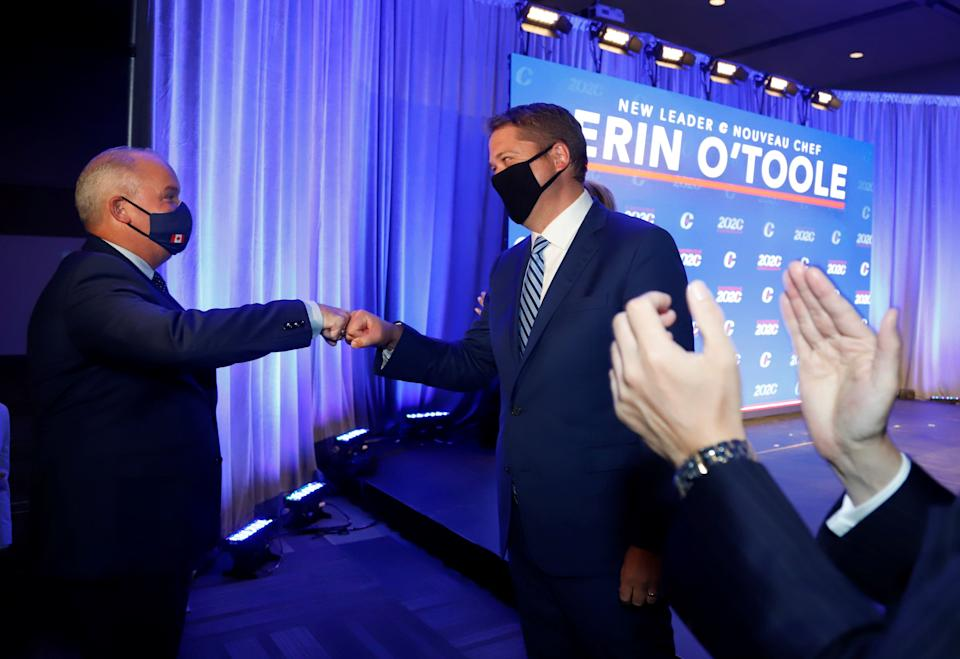 Erin O'Toole, the new leader of Canada's Conservative party, fist bumps outgoing leader Andrew Scheer before giving his victory speech in Ottawa, Aug. 24, 2020. (Photo: Patrick Doyle / Reuters)