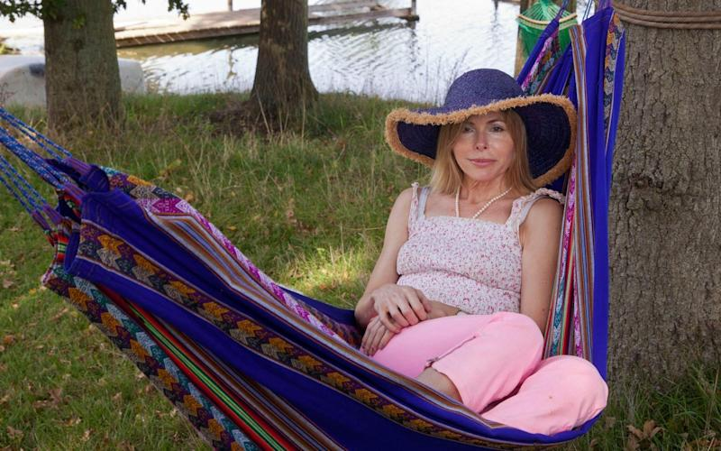 Julia Stephenson, who is wearing pink trousers and wide-brimmed hat, sits in a hammock by a river - Eyevine/David Sandison