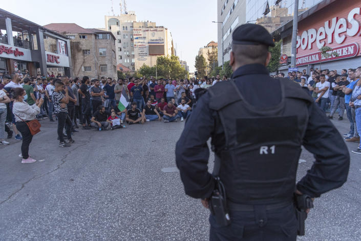 Demonstrators close the road in front of riot police during a rally protesting the death of Palestinian Authority outspoken critic Nizar Banat, in the West Bank city of Ramallah, Saturday, July 3, 2021. Hundreds of Palestinians gathered to demonstrate against President Mahmoud Abbas, hoping to inject new momentum into a protest movement sparked by the death of an outspoken critic in the custody of security forces. (AP Photo/Nasser Nasser)