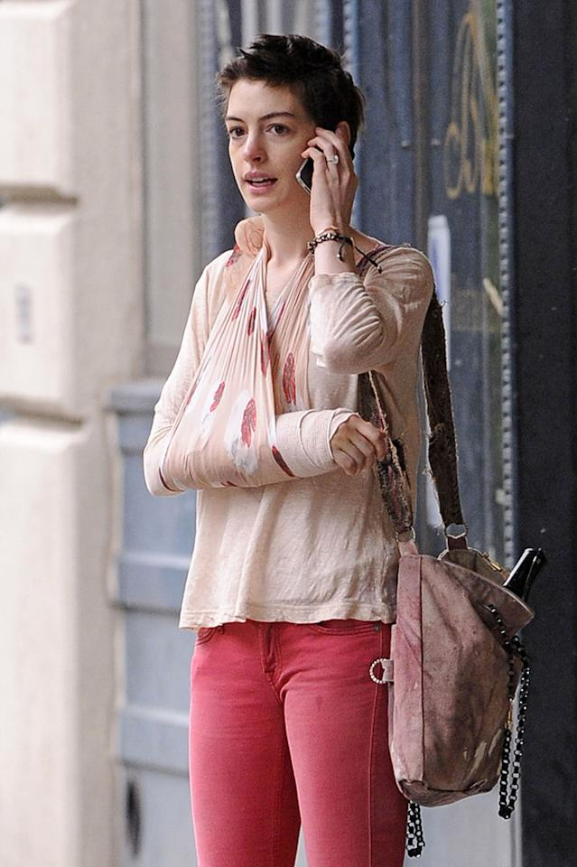 Anne Hathaway cradles her injured arm as she and fiance Adam Shulman are seen outside their apartment in Brooklyn