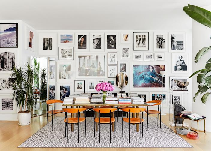 """""""In Milan, I've had mirrored walls everywhere—it just doubles the size. And we are obsessed with this vintage mirrored screen. By putting it in the dining room, we can bring the skyline view right to the table,"""" says Atwood. Both the dining room table and chairs are vintage, and while the couple does entertain, the table doubles as a library of sorts. Explains Deutsch, """"It's modern living here, and we eat at the bar in the kitchen 90% of the time."""" Vintage Versace plates are on display, as well. (Atwood was once head of accessories design at the storied house.)"""
