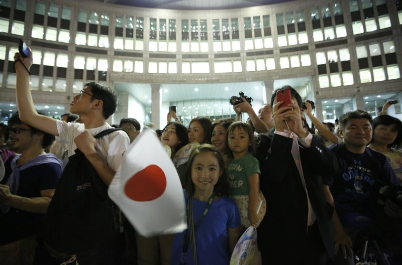 "Girl waves a Japan national flag as visitors take photos during an event titled ""Tokyo 2020 Host City Welcoming Ceremony"", upon the delegation's return, at the Tokyo Metropolitan Government Building in Tokyo"