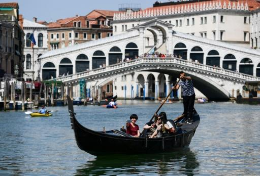 A gondolier rows tourists along the Grand Canal in Venice, a more traditional sight than the massive cruise ships which now visit the historic city