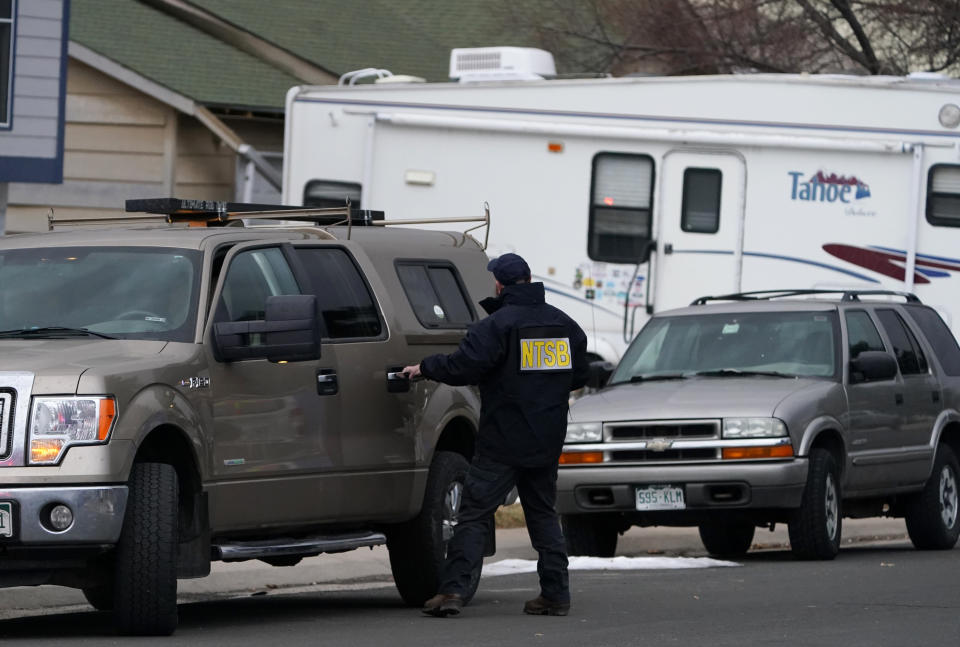 A National Transportation Safety Board investigator exits his vehicle near a home peppered by parts from a plane as it was making an emergency landing at nearby Denver International Airport Saturday, Feb. 20, 2021, in Broomfield, Colo. (AP Photo/David Zalubowski)