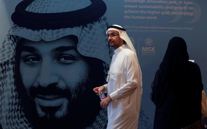 A participant walks next to a picture of Saudi Crown Prince Mohammed bin Salman during the Misk Global Forum in Riyadh - REUTERS