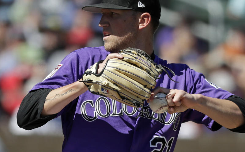 FILE - In this March 18, 2019, file photo, a tattoo of mountains extends down the right arm of left-handed Colorado Rockies starting pitcher Kyle Freeland as he throws against the Cincinnati Reds in a spring training baseball game in Scottsdale, Ariz. Denver native Kyle Freeland wears the affection for his city on his right arm: Tattoos of the area code (303), the elevation (5,280) and a silhouette of the Rocky Mountains. (AP Photo/Elaine Thompson, File)