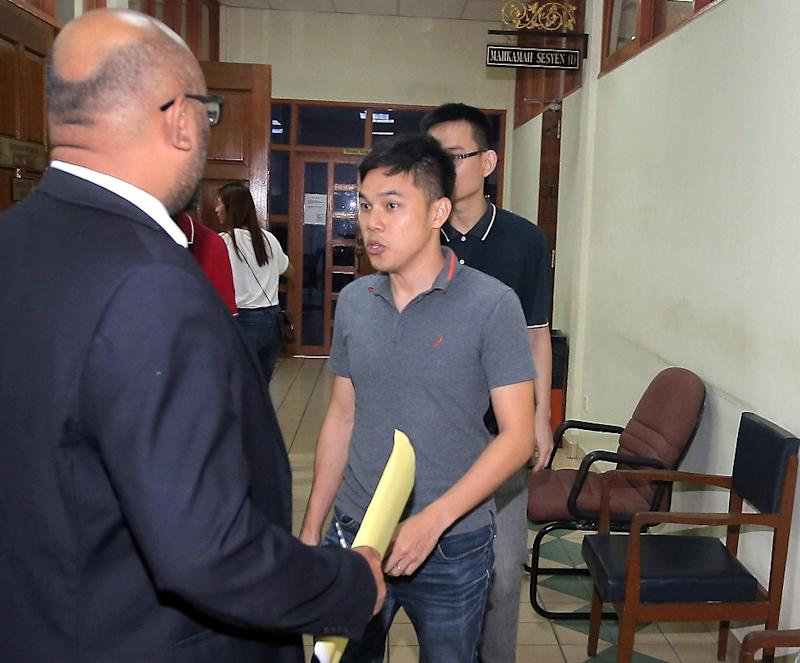 Yap Ying Chao (back, partially visible) and Boo Weil Seng (centre) claimed trial at the Sessions court for illegal deposit taking, in Taiping September 7, 2018. — Picture by Farhan Najib