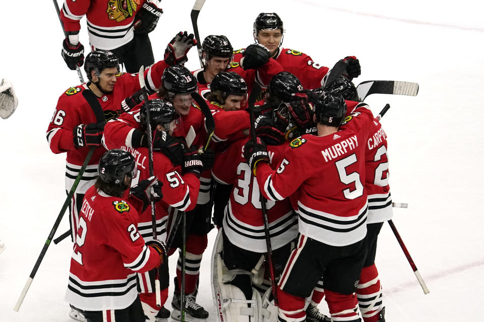 Chicago Blackhawks goalie Malcolm Subban (30) celebrates with teammates after they defeated the Tampa Bay Lightning in a shootout of an NHL hockey game in Chicago, Friday, March 5, 2021. (AP Photo/Nam Y. Huh)