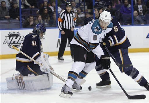 San Jose Sharks' Joe Pavelski (8) works for position with St. Louis Blues' Barret Jackman (5) as goalie Jaroslav Halak (41) watches the loose puck in the first period of an NHL hockey game Sunday, Feb. 12, 2012, in St. Louis.(AP Photo/Tom Gannam)