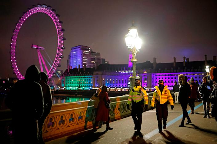 Police officers disperse people on Westminster Bridge in a near-deserted London on New Year's Eve, December 31, 2020, as authorities hope the message to stay at home is obeyed.