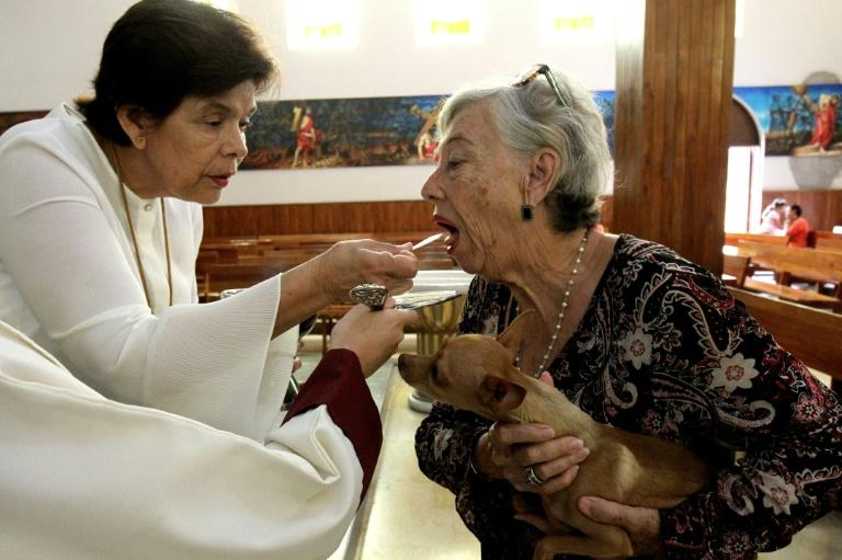 A catholic faithful receives the Eucharist as she brings her pet to be blessed at the Church of Saint Francis of Assisi, patron saint of animals, whose feast marks World Animal Day in Zapopan, Jalisco state in Mexico, on October 4, 2019 (AFP Photo/ULISES RUIZ)