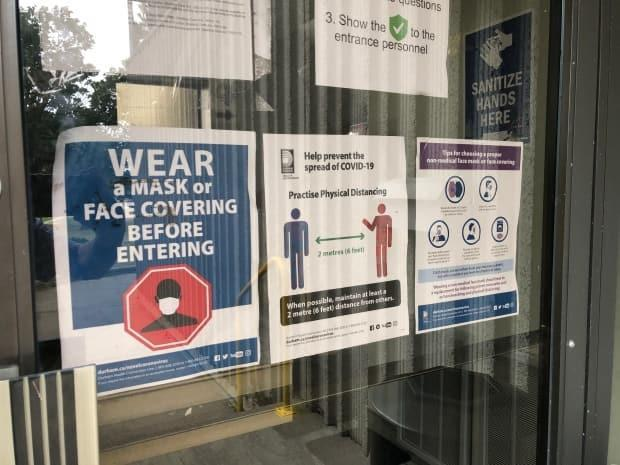 COVID-19 signs, urging people to wear masks and keep their distance, are displayed on a glass door at Playground Global facility in Oshawa. COVID-19 cases are linked to three separate basketball tournaments at this facility. (Greg Bruce/CBC - image credit)