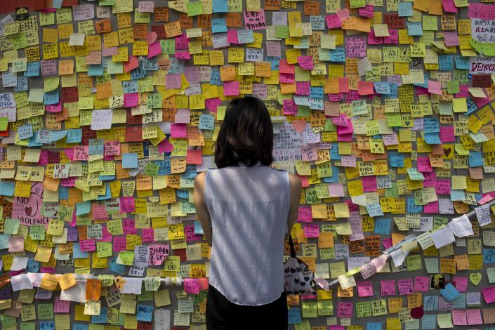 A woman looks at messages of support for pro-democracy demonstrations on a wall, as protesters block areas around government headquarters in Hong Kong October 7,2014. Pro-democracy demonstrations in Hong Kong rolled into early Tuesday with hundreds of students remaining camped out in the heart of the city after more than a week of rallies and behind-the-scenes talks showing modest signs of progress. REUTERS/Tyrone Siu (CHINA - Tags: POLITICS CIVIL UNREST CRIME LAW)