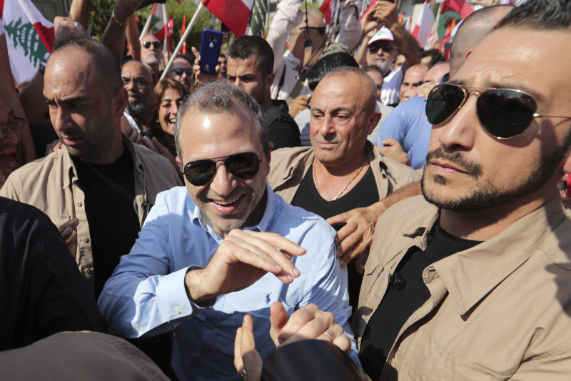 Head of the Free Patriotic Movement and Lebanese Foreign Minister Gebran Bassil, center, escorted by his bodyguards, greets supporters during a protest near the presidential palace in the Beirut suburb of Baabda, Lebanon, Sunday, Nov. 3, 2019. Thousands of people are marching to show their support for Aoun and his proposed political reforms that come after more than two weeks of widespread anti-government demonstrations. (AP Photo/Hassan Ammar)