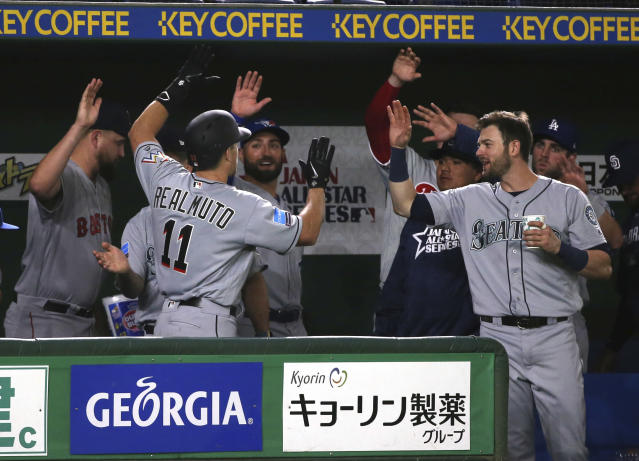 MLB All-Star's J.T. Realmuto (11) of the Miami Marlins is celebrated by teammates after hitting a solo home-run off Yomiuri Giants pitcher Ryusei Oe in the fifth inning of their exhibition baseball game at Tokyo Dome in Tokyo, Thursday, Nov. 8, 2018. (AP Photo/Toru Takahashi)