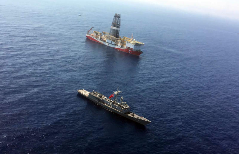 FILE - In this Tuesday, July 9, 2019 file photo, a Turkish Navy warship patrols near Turkey's drilling ship ' Fatih ' that is making its way towards the eastern Mediterranean near Cyprus. Turkish officials say the drillships Fatih and Yavuz will drill for gas, which has prompted protests from Cyprus. (Turkish Defence Ministry via AP, Pool)