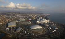 "An aerial view from a helicopter shows the Olympic Park under construction in the Adler district of the Black Sea resort city of Sochi, December 23, 2013. Sochi will host the 2014 Winter Olympic Games in February. The view shows (clockwise from R, top) the ""Fisht"" Olympic Stadium, the ""Shayba"" Arena, the ""Bolshoy"" Ice Dome, the ""Ice Cube"" Curling center, the ""Adler Arena"" and the ""Iceberg"" Skating Palace. Picture taken December 23, 2013. REUTERS/Maxim Shemetov (RUSSIACITYSCAPE OLYMPICS - Tags: CITYSPACE BUSINESS CONSTRUCTION SPORT OLYMPICS) CITYSCAPE"
