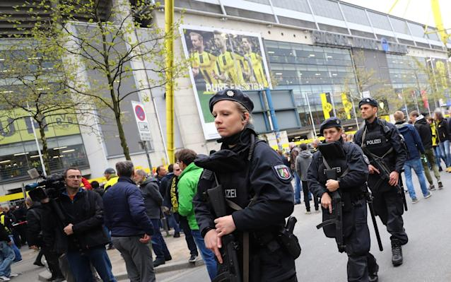 <span>Police officers outside the stadium before the match</span> <span>Credit: Kai Pfaffenbach/Reuters </span>
