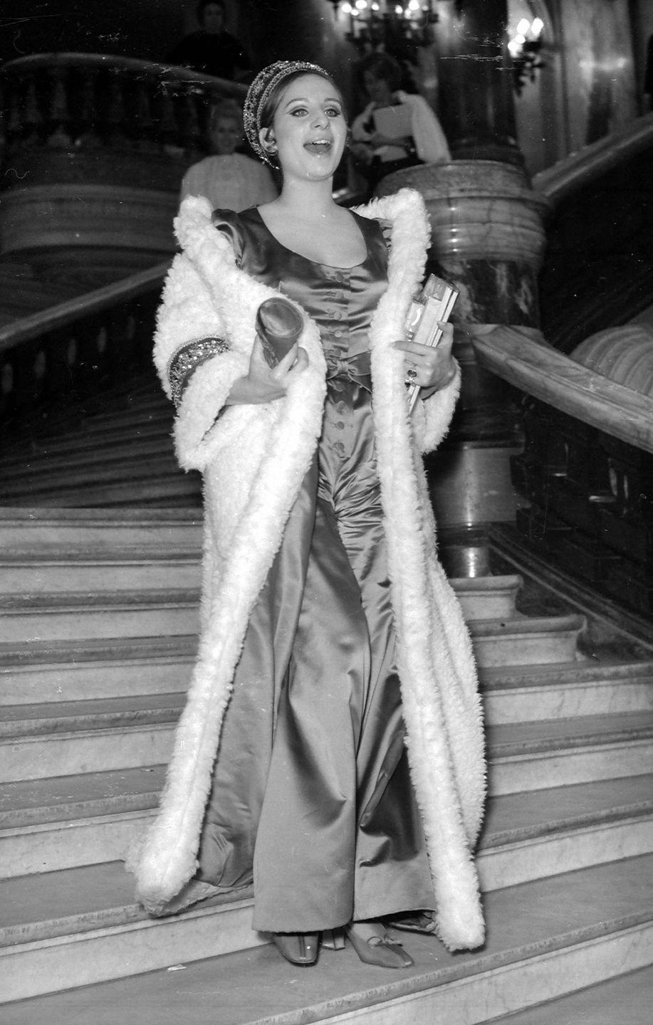 <p>Barbra Streisand looks beautiful in an evening gown and fur coat as she makes her way down a staircase at the Palais Garnier opera house.</p>