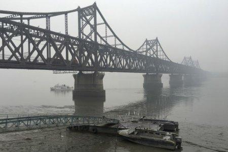 Trucks move across the bridge linking North Korea with the Chinese border city of Dandong in this March 3, 2016 file photo. REUTERS/Megha Rajagopalan