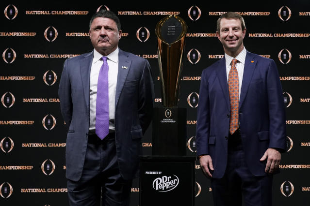 LSU head coach Ed Orgeron, left, and Clemson head coach Dabo Swinney pose with the trophy after a news conference for the NCAA College Football Playoff national championship game Sunday, Jan. 12, 2020, in New Orleans. Clemson is scheduled to play LSU on Monday. (AP Photo/Chris Carlson)