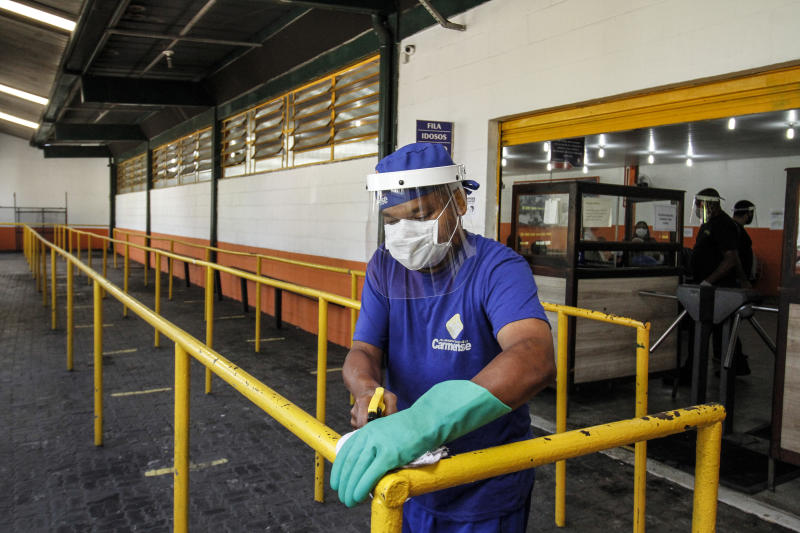 NITEROI, BRAZIL - AUGUST 05: An employee wearing a face cleans a handrail at a popular soup kitchen on August 5, 2020 in Niteroi, Brazil. Employees received special training to ensure the safety of visitors. The site will intensify the cleaning process and will operate at 50% capacity and with customers spaced at the tables to maintain social distance. (Photo by Luis Alvarenga/Getty Images)