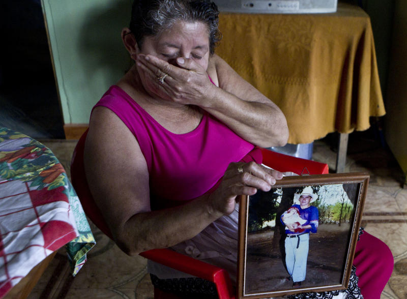 Maria Alvarenga, holding a photograph of her son Jose Salvador Alvarenga, put her hand over her mouth during an interview inside her home, in the village of Garita Palmera, El Salvador, Tuesday, Feb. 4, 2014. The account of her son's survival after more than 13 months in an open boat has proven a double miracle for his family, who lost touch with him years ago and thought he was dead. Jose Salvador Alvarenga said he left Mexico in December 2012 for a day of shark fishing and ended up on the remote Marshall Islands. (AP Photo/Esteban Felix)