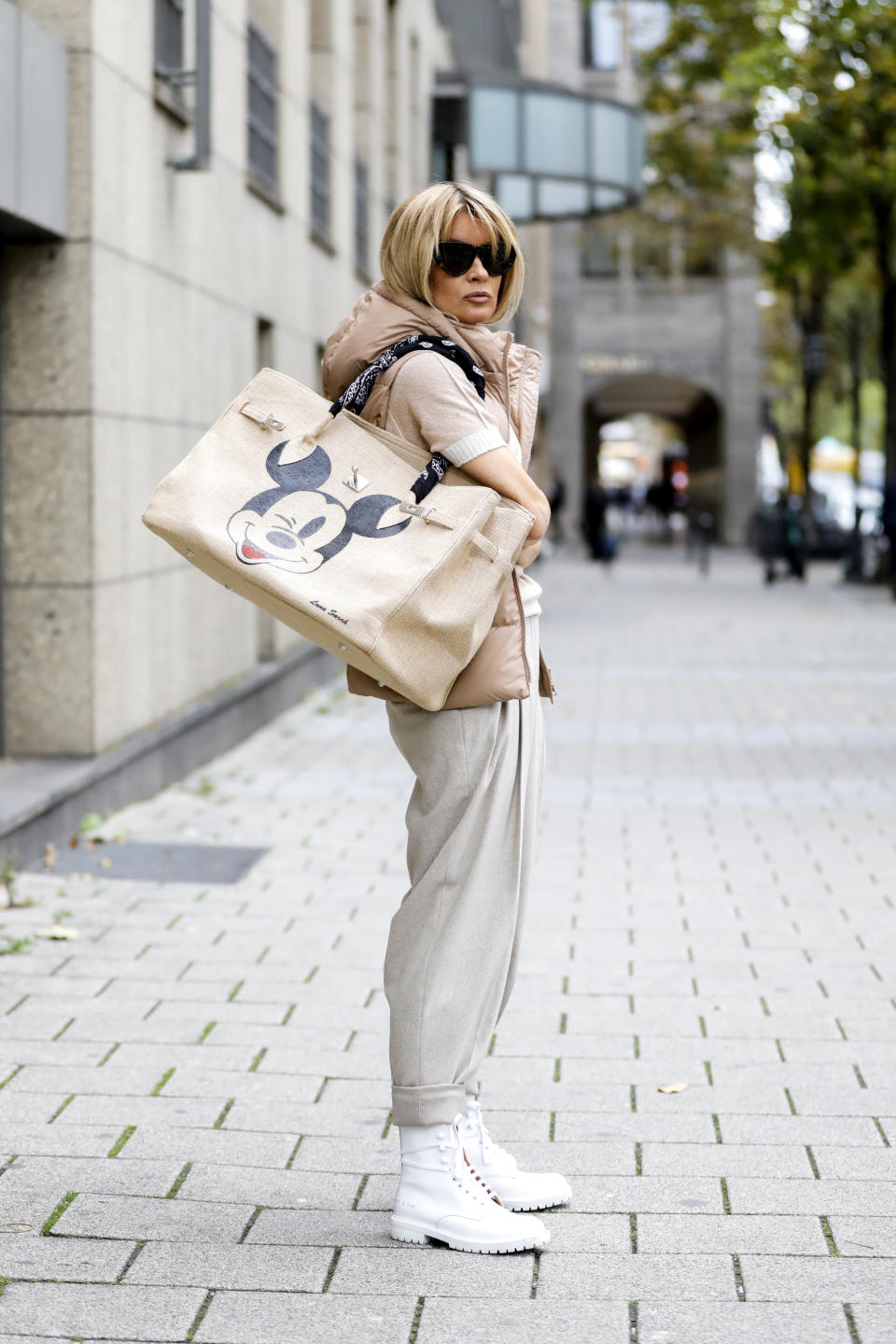 DUSSELDORF, GERMANY - OCTOBER 23: Influencer Gitta Banko, wearing a beige short sleeve turtleneck pullover, a beige vest with hood and beige pants by Madeleine, white boots by Common Project, a beige bast bag with Micky Mouse by Luna Sarah and sunglasses by Bottega Veneta, during a street style shooting on October 23, 2020 in Dusseldorf, Germany. (Photo by Streetstyleshooters/Getty Images)