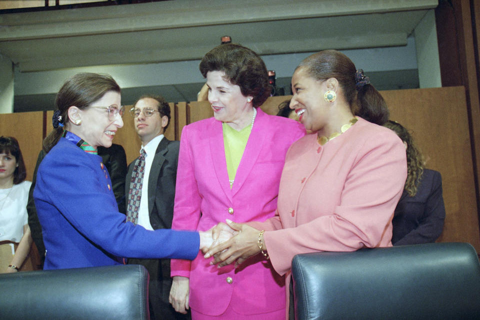 Supreme Court nominee Judge Ruth Bader Ginsburg, left, shakes hands with Sen. Carol Moseley-Braun, D-Ill., as Sen. Dianne Feinstein, D-Calif., looks on prior to Ginsburg's confirmation hearing before the Senate Judiciary Committee on Capitol Hill (Photo: Doug Mills/AP)
