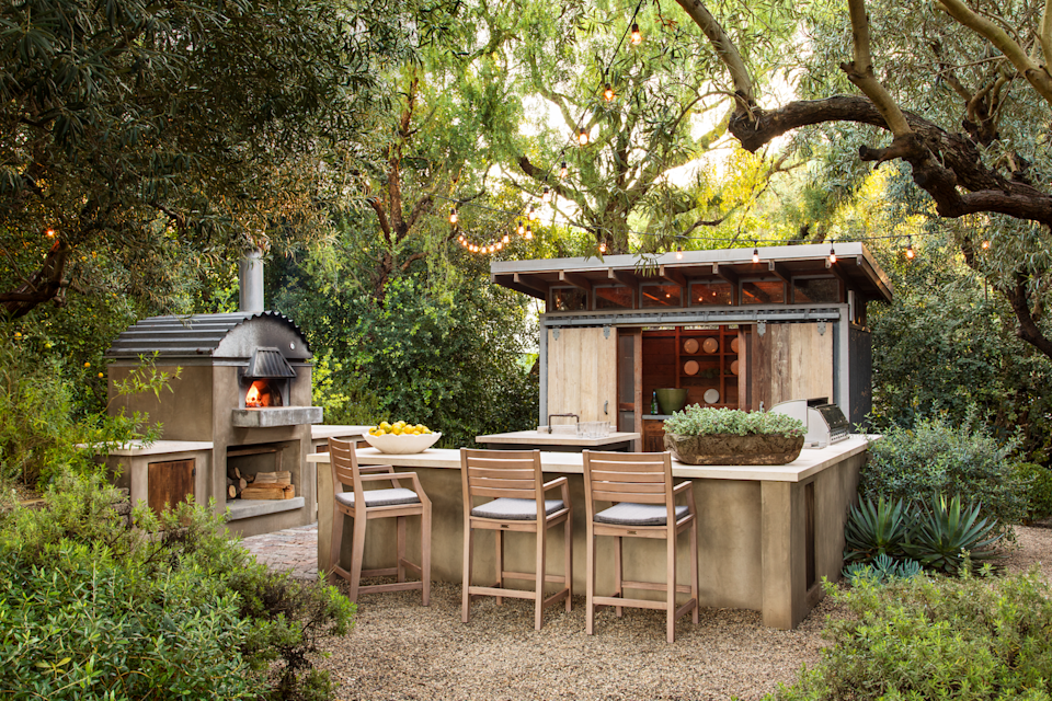 """<p><a href=""""https://www.shraderdesign.com/"""" rel=""""nofollow noopener"""" target=""""_blank"""" data-ylk=""""slk:Scott Shrader"""" class=""""link rapid-noclick-resp"""">Scott Shrader</a> transformed an oversize Malibu backyard into distinct outdoor living areas, maximizing the lush space on the property. This hidden kitchen and bar, complete with a wood oven for homemade pizzas, grill, sink, and plenty of storage space, which makes this outdoor kitchen ideal for drinking and dining alfresco. </p>"""