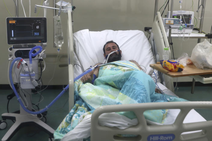 An Iraqi patient infected with COVID-19 lies on a medical bed at the intensive care unit of the Rafik Hariri University Hospital in Beirut, Lebanon, Friday, Jan. 22, 2021. Hospitals in Lebanon are reaching full capacity amid a dramatic surge in coronavirus cases across the crisis-hit Mediterranean nation even amid strict lockdown. (AP Photo/Bilal Hussein)