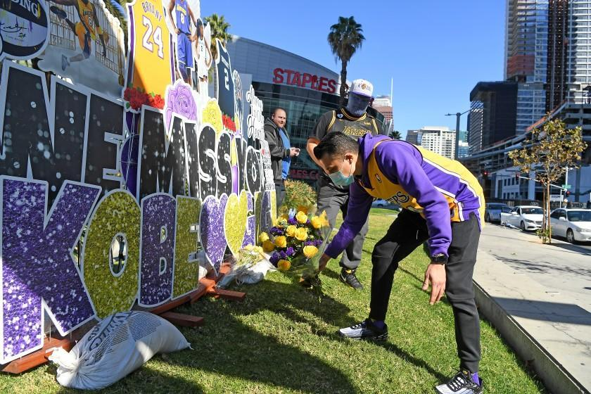 LOS ANGELES, CALIFORNIA JANUARY 26, 2021-Nestor Magana lays places flowers in front of a Kobe Bryant mural on the 1-year anniversary of Kobe Bryant's death in Downtown Los Angeles Tueswday. (Wally Skalij/Los Angeles Times)