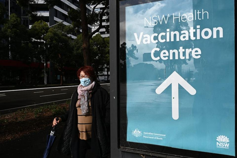 A woman walks past the vaccination centre signage in Sydney.