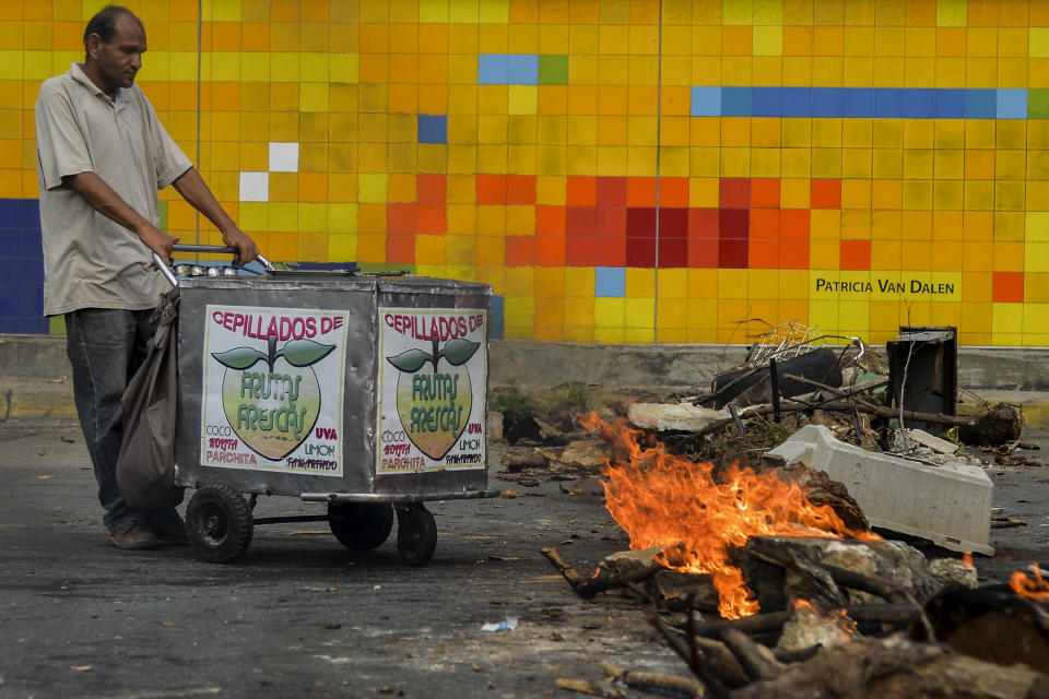 An ice-cream vendor remains by a roadblock during a protest against Venezuelan President Nicolas Maduro in Caracas, on June 14, 2017. (Photo: LUIS ROBAYO/AFP/Getty Images)