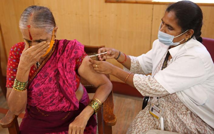 A woman receives a dose of a Covid-19 vaccine in Bangalore, India on 13 August 2021 - Jagadeesh Nv/Shutterstock