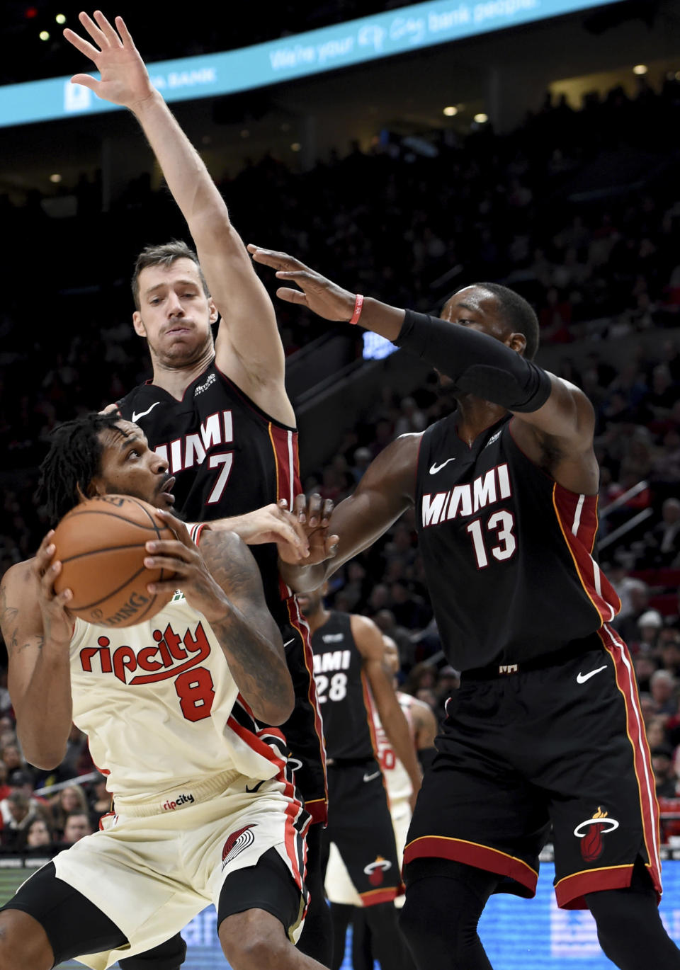 FILE - Portland Trail Blazers forward Trevor Ariza, left, tries to go up for a shot on Miami Heat guard Goran Dragic, center, and forward Bam Adebayo, right, during the second half of an NBA basketball game in Portland, Ore., in this Sunday, Feb. 9, 2020, file photo. Ariza has had interest in playing for the Miami Heat since a draft workout in 2004. He was traded to Miami this week and now gets that long-awaited chance. (AP Photo/Steve Dykes, File)