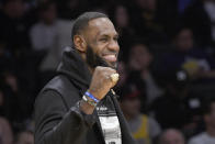 Los Angeles Lakers injured guard LeBron James cheers his team during the first half of an NBA basketball game against the Denver Nuggets on Sunday, Dec. 22, 2019, in Los Angeles. The Nuggets won 128-104. James sat out the game because of a thoracic muscle strain. (AP Photo/Michael Owen Baker)