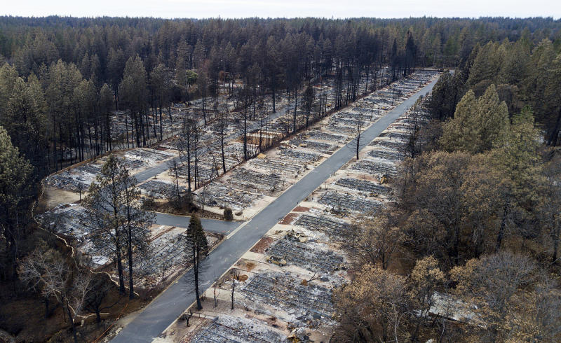 FILE - This Dec. 3, 2018, file photo, shows homes leveled by the Camp Fire line at the Ridgewood Mobile Home Park retirement community in Paradise, Calif. Pacific Gas & Electric officials are to be expected to appear in court Tuesday, June 16, 2020, to plead guilty for the deadly wildfire that nearly wiped out the Northern California town of Paradise in 2018. (AP Photo/Noah Berger, File)