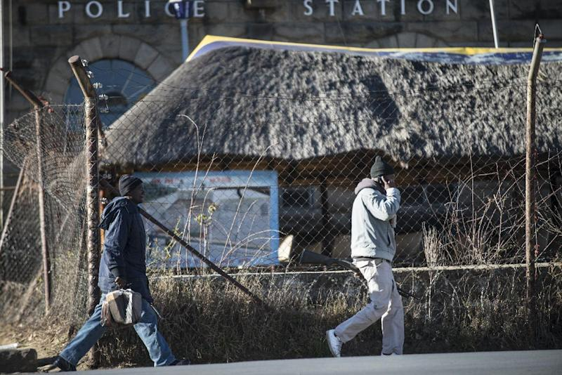 Two armed policemen leave the Maseru Central Charge Office police station on August 30, 2014, in downtown Maseru, Lesotho (AFP Photo/Mujahid Safodien)