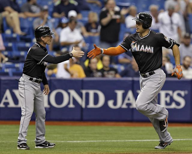 Miami Marlins' Giancarlo Stanton, right, reaches out to shake hands with third base coach Brett Butler after his two-run home run off Tampa Bay Rays relief pitcher Brad Boxberger during the seventh inning of an interleague baseball game Thursday, June 5, 2014, in St. Petersburg, Fla. Marlins' Donovan Solano also scored on the hit. (AP Photo/Chris O'Meara)