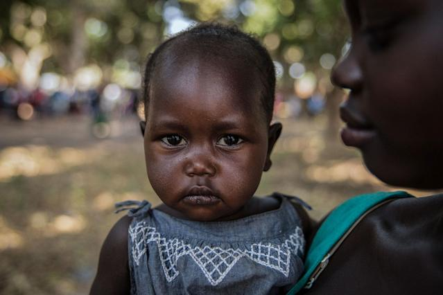 <p>Najat (R), 17, who was raped numerous times by a soldier, holds her one-year-old daughter Eva during a release ceremony for child soldiers in Yambio, South Sudan on Feb. 7, 2018. (Photo: Stefanie Glinski/AFP/Getty Images) </p>