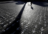 A woman walks by thousands of crosses that are painted at the Old Town Square, to commemorate the 1-year anniversary of the death of first Czech COVID-19 patient, in Prague, Czech Republic, Monday, March 22, 2021. Some 25,000 have been killed by COVID-19 in the hard-hit Czech Republic. Jaromir Vytopil was one of them. His everyday presence in the small Czech town of Pelhrimov was something everybody took for granted for seven decades as he had served the generations of readers. The longest serving Czech bookseller, passed away on Nov 9. 2020, at age of 83. (AP Photo/Petr David Josek)