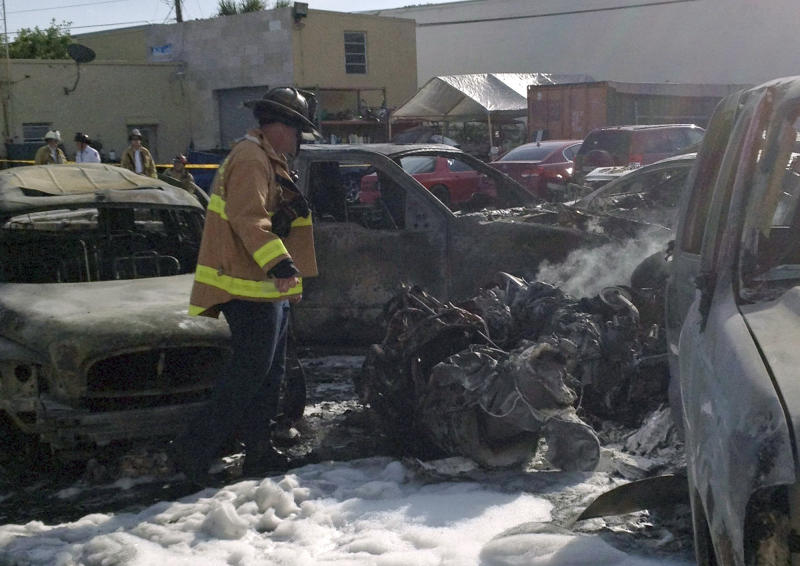 A Fort Lauderdale Fire Rescue worker checks a part of the Piper PA31 twin-engine that crashed shortly after takeoff  from Fort Lauderdale Executive Airport into a parking  lot east of the Airport in Fort Lauderdale, Fla., Friday, March 15, 2013. All three aboard the plane were killed. No one on the ground was hurt. (AP Photo)