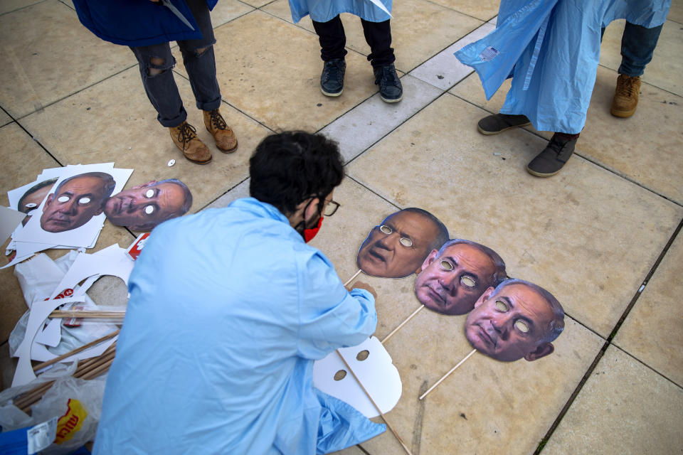 Israeli demonstrators prepare masks depicting Israeli Prime Minister Benjamin Netanyahu and Israeli Defense Minister Benny Gantz during a protest against a parliamentary vote to dissolve the Knesset and send the country to its fourth elections in two years while it still hasn't approved a national budget for 2020, in Tel Aviv, Wednesday, Dec. 2, 2020. (AP Photo/Oded Balilty)