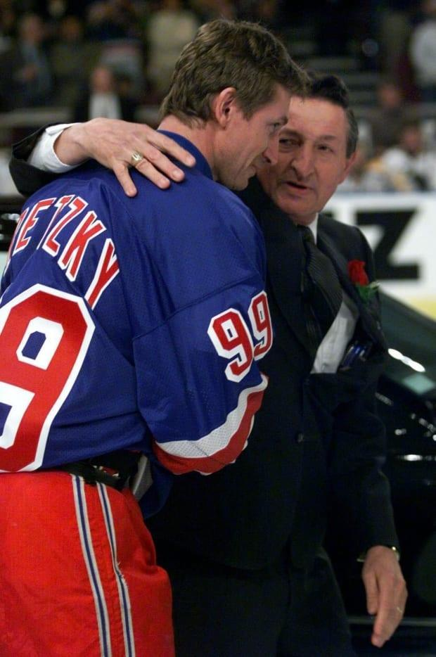 Wayne Gretzky is hugged by his father, Walter, after being presented with a car during the pre-game ceremonies for Gretzky's last game in the NHL, as a New York Ranger, on April 18, 1999. (Paul Chiasson/The Canadian Press - image credit)