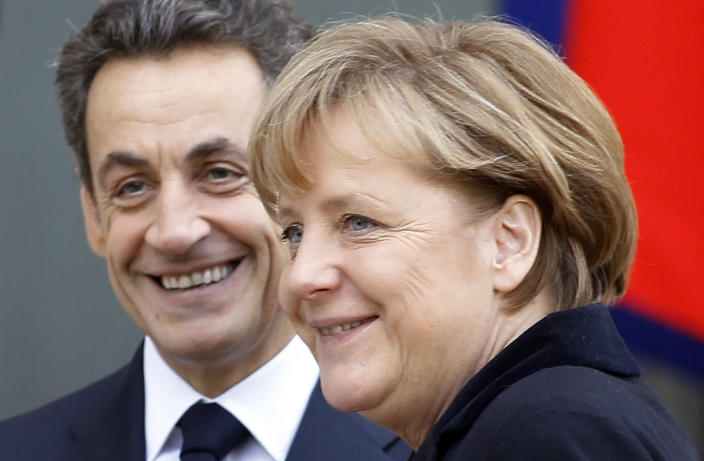 FILE - In this Dec. 5, 2011, file photo, French President Nicolas Sarkozy, left, smiles as he greets German Chancellor Angela Merkel prior to their meeting at the Elysee Palace in Paris. A Paris court on Monday found former President Sarkozy guilty of corruption and influence peddling and sentenced him to one year in prison and a two-year suspended sentence. (AP Photo/Remy de la Mauviniere, File)