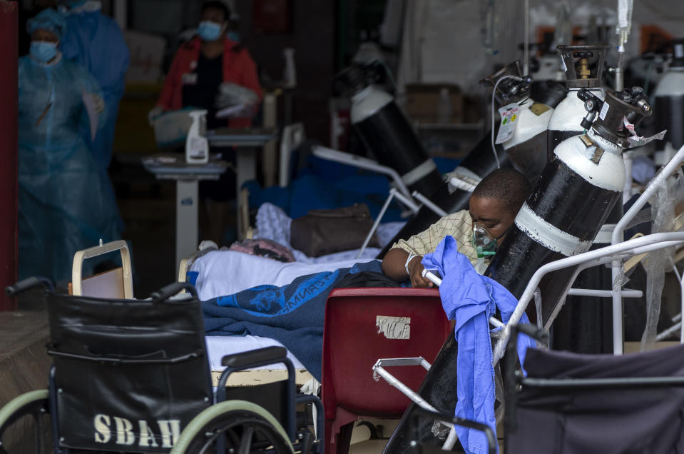 A patient wearing an oxygen mask is being treated in the makeshift emergency unit at Steve Biko Academic Hospital in Pretoria, South Africa, Monday, Jan. 11, 2021, which is battling an ever-increasing number of Covid-19 patients. (AP Photo/Themba Hadebe)