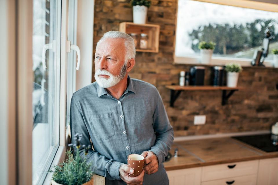 Portrait of a senior man standing in the kitchen and looking through window, holding a cup of coffee or tea on winter day.